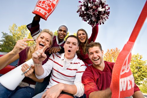six people cheering at a football game