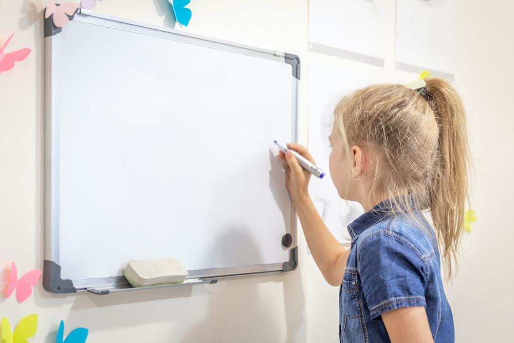 Little girl writing on empty whiteboard with a marker pen. Learning, education and back to school concept with copy space