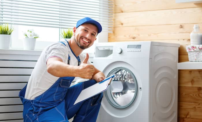 a repair man fixing a washing machine